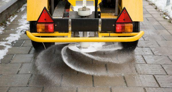 A machine is sprinkling salt on a sidewalk